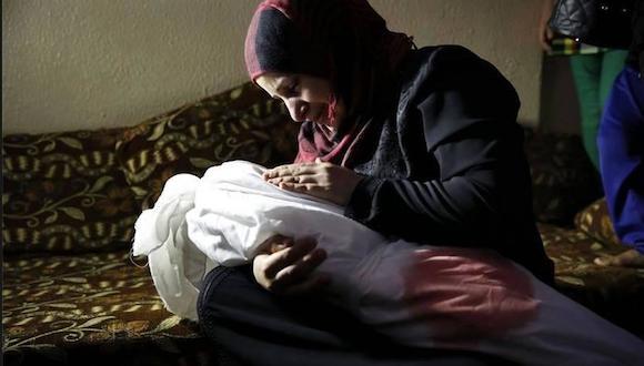 Una madre da el último adiós a su pequeño hijo, asesinado por Israel hace pocas horas. Foto: Twitter