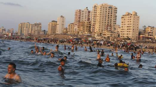 Palestinians swim in the Mediterranean Sea off the coast of Gaza City