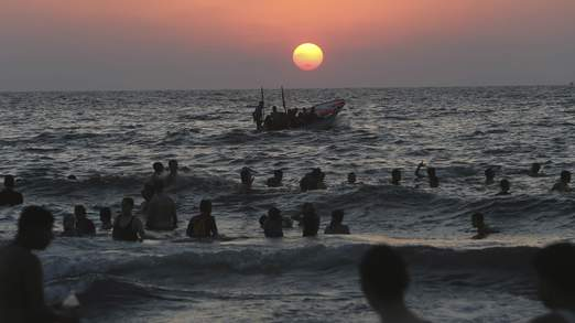 Palestinians swim in the Mediterranean Sea off the coast of Gaza City during sunset