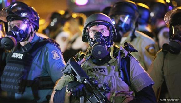Agentes antidisturbios avanzan contra los manifestantes en el centro de Ferguson.