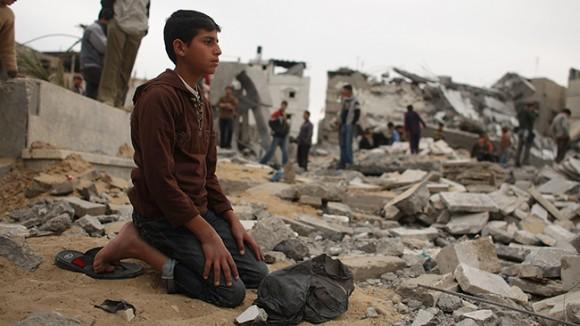 Un niño reza en las ruinas de una mezquita dañada por las tropas israelíes el 23 de enero de 2009 en un suburbio muy dañada en la Ciudad de Gaza, Franja de Gaza.