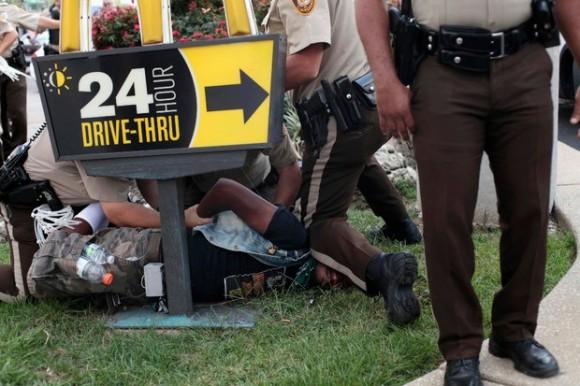 Policías detienen a un manifestante que protestaba por la muerte del joven afroamericano Michael Brown, a menos de un policía en Ferguson, Missouri. Foto Reuters