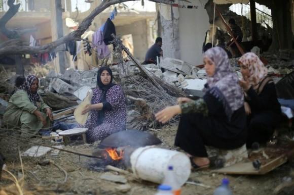 Mujeres palestinas hornean pan este jueves delante de los restos de su casa destruida en Khan Younis. Foto Reuters.
