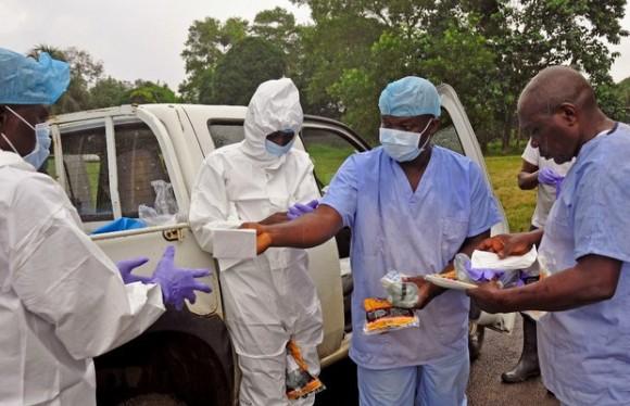17 Ébola 01.jpg Trabajadores de salud se reparten equipos de protección antes de recoger cadáveres de personas que murieron por ébola en las calles de Monrovia, Liberia, el 16 de agosto de 2014. Foto Ap
