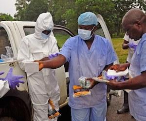 Trabajadores de salud se reparten equipos de protección antes de recoger cadáveres de personas que murieron por ébola en las calles de Liberia