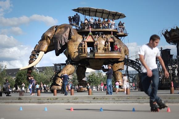 Turistas disfrutan en un elefante mecánico en Francia. Foto: Jean-Sebastien Evrard/AFP.