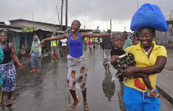 La gente celebra en las calles de West Point que las autoridades hayan puesto fin al bloqueo de una semana de ese vecinario en Liberia el 30 de agosto del 2014. La cuarentena tuvo por objeto contener la propagación del brote de bola. Foto: ABBAS DULLEH
