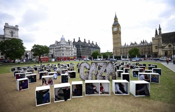 Los voluntarios se sientan en cajas de madera en la Plaza del Parlamento, para representar las condiciones de vida en Gaza, durante una protesta en Londres el 14 de agosto de 2014 Algunos de ciento cincuenta hombres, mujeres y niños hacinados en cajas, en un intento de ilustrar las condiciones que enfrenta el pueblo de Gaza atrapada por el bloqueo, en un evento organizado por Oxfam. REUTERS / Dylan Martinez