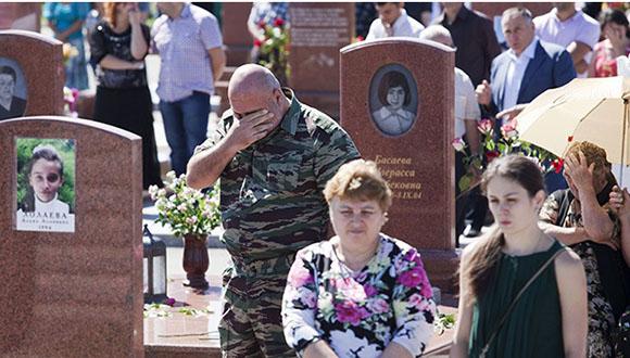 Familiares de las víctimas de Beslán, en el cementerio. Imagen de 2013. Foto: EFE.