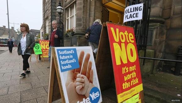 Carteles a favor y en contra de la independencia fuera de un centro electoral. Foto / Reuters.