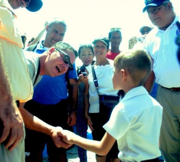 Patrick Hemingway, nieto del novelista estadounidense Ernest Hemingway, conversa con un pionero residente en la zona, que asiste a recibirlos en la localidad capitalina de Cojímar a su arribo para celebrar el aniversario 80 de la llegada de su abuelo a La Habana en el simbólico yate El Pilar. Cojimar, La Habana, Cuba, 8 de septiembre de 2014.   AIN FOTO/Oriol de la Cruz ATENCIO