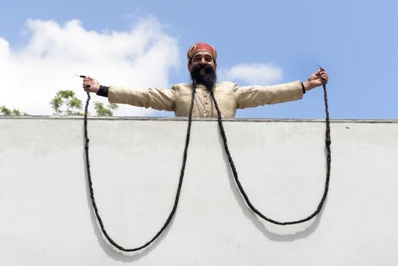 Un hombre indio enseña su extensa barba de 18 pies de largo, India. Foto: AFP / Sam Panthaky