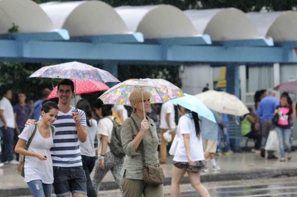 Personas protegiéndose de la lluvia mientras cruzan  la Calle 23, en El Vedado, La Habana, Cuba