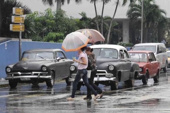 Dos mujeres se cubren  de la lluvia mientras cruzan por la esquina de las calles 23 y L.