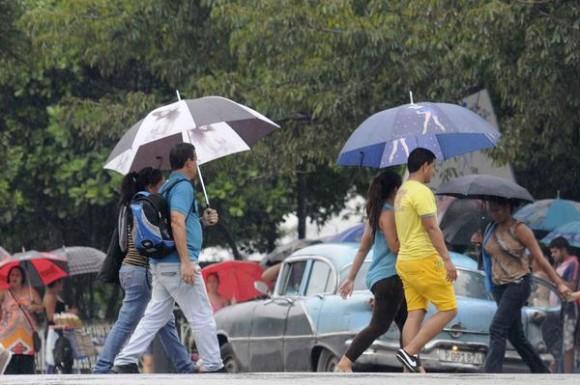 Personas protegiéndose de la lluvia mientras cruzan por la esquina de las calles 23 y L, en El Vedado