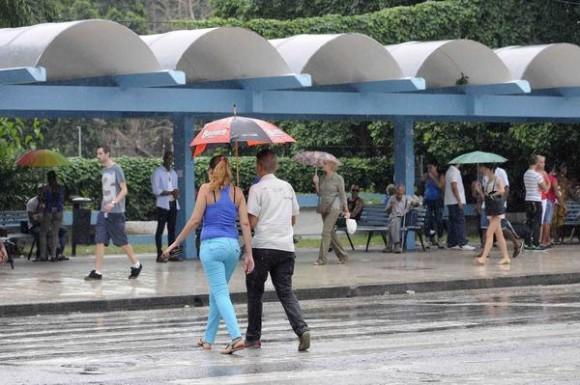 Personas protegiéndose de la lluvia mientras cruzan la Calle 23