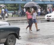 Dos muchachas se protegen de la lluvia mientras cruzan la Calle 23,  en El Vedado,