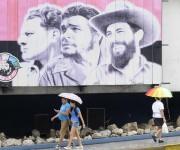 Personas protegiéndose de la lluvia mientras transitan por El Vedado