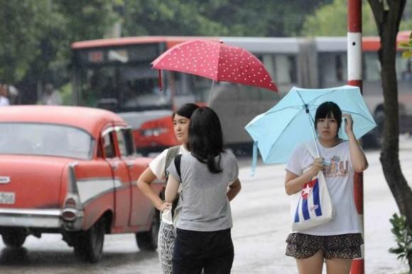 Jóvenes se cubren de la lluvia  en El Vedado