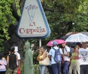 Personas protegiéndose de la lluvia mientras hacen  la cola para entrar a la Heladería Coppelia