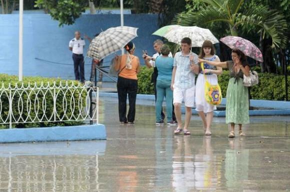Personas protegiéndose de la lluvia mientras salen de la Heladería Coppelia