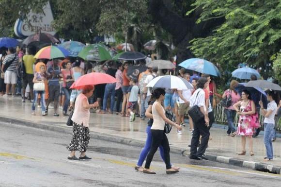Personas protegiéndose de la lluvia mientras cruzan  por la esquina de las calles 23 y L