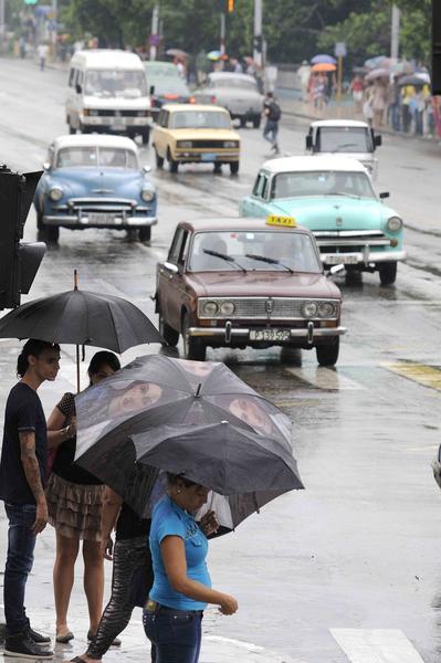 Personas se  protegen de la lluvia mientras esperan  para  cruzar por la esquina de las calles 23 y M