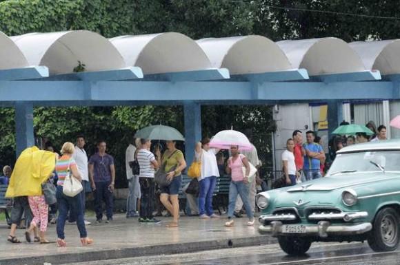 Personas protegiéndose de la lluvia mientras transitan por El Vedado.