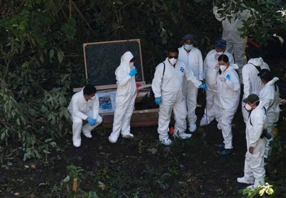Trabajadores forenses buscan restos humanos por debajo de una ladera llena de basura en las montañas boscosas cerca de Cocula, en el estado mexicano de Guerrero, el martes 28 de octubre de 2014. Los sospechosos arrestados esta semana dijeron a los fiscales que muchos de los 43 estudiantes que desaparecieron el 26 de septiembre en la ciudad de Iguala fueron retenidos cerca de este lugar. Foto: Rebecca Blackwell, Pool/AP