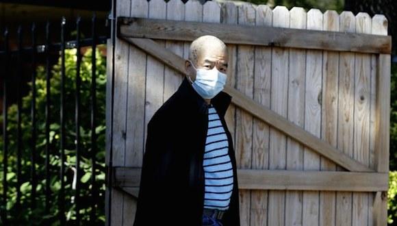 Un hombre porta una mascarilla afuera del completo de departamentos donde permanece aislado Eric Duncan, el primer paciente contagiado de ébola que viajó de Liberia a Dallas. Foto: Ap.