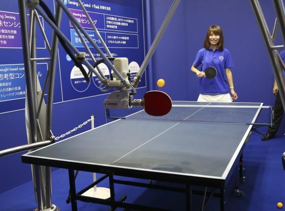 """Pese a su intimidante parecido a una araña, el robot de tres patas de OMRON Corp. es un oponente tranquilo en ping-pong. Observa a su oponente humano para predecir el sendero de la pelota. Aun así, el robot no dificulta las cosas y falla disparos de vez en cuando. Con cinco motores para controlar el movimiento de la paleta, está programado para enviar el servicio de una forma que resulta fácil a sus rivales. """"Este robot de ping-pong es realmente una demostración de cómo un robot puede interactuar con una persona y reaccionar de forma apropiada"""", dijo Takuya Tsuyuguchi, un gerente de Omron. """"Nosotros vemos a este robot en el futuro siendo usado quizás en una fábrica o en una línea de producción, en un papel en el que tendría que interactuar con un trabajador para hacer o construir algo. Esto involucraría que el robot comprendiera las necesidades de su contraparte humana y respondiera apropiadamente"""".  Mostrado en la Expo de Tecnologías de Avanzada de Japón CEATEC en Chiba, cerca de Tokio. Martes 7 de octubre de 2014. AP Photo/Koji Sasahara / Cubadebate"""