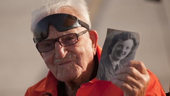 """Tom Lackey, un acróbata británico de 94 años, desafió este sábado los límites de la naturaleza con una nueva hazaña que le ha permitido volar con el cuerpo atado a un avión biplano """"Boeing Stearman"""" alrededor del peñón de Gibraltar. Llevaba una foto de su esposa. Foto: AFP"""