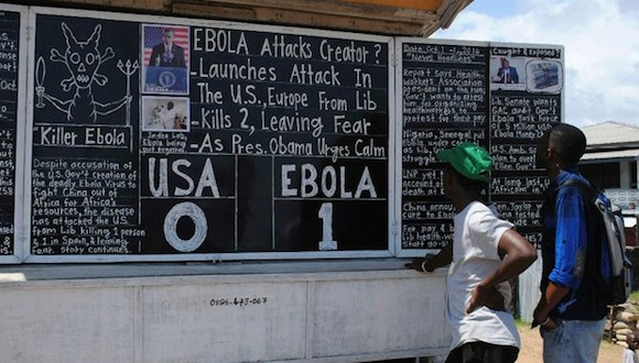 "Transeúntes leen titulares de del periódico mural Daily Talk escritos en una pizarra: ""Ébola 1 : EU 0"", en Monrovia. Foto: Reuters"