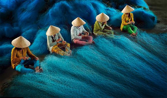 Trabajadores arreglando redes en una fábrica de Bac Lieu, en Vietnam, esta fotografía ganó el premio correspondiente a Asia y el Pacífico.