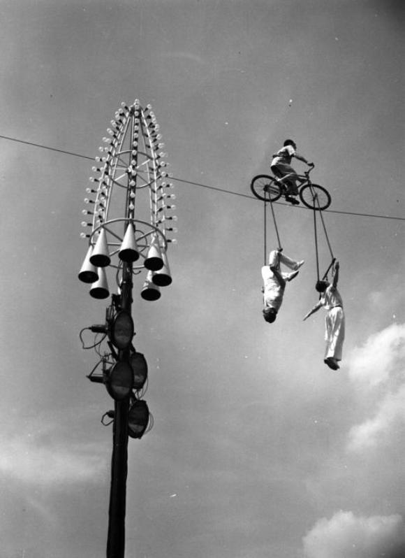 El Mestelrich Trio, grupo español formado por un ciclista que pedalea sobre cuerdas flojas, y otros dos trapecistas que se mantienen en vilo, actúan sobre los jardines Battersea, en Londres.