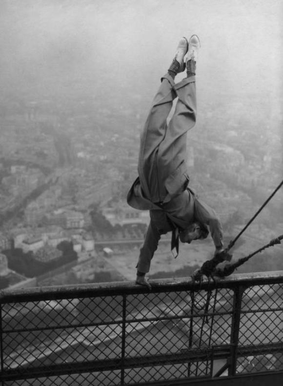El doble de un actor realiza equilibrios sobre una barandilla de la parte superior de la Torre Eiffel, París, alrededor de 1935.