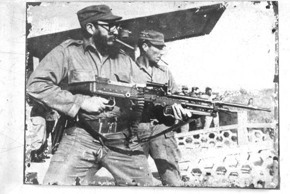 Fidel en práctica de tiro probando una ametralladora de trípode sostenida en las manos. La foto estaba dentro de un cuarto que sirvió de laboratorio fotográfico en el CENSA. Autor desconocido.