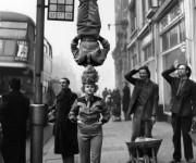 Los transeúntes se paraban para mirar a estos dos miembros del Bertram Mills Circus, que caminaban por la acera de Hammersmith Broadway, uno sobre la cabeza del otro.