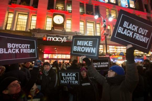 Manifestantes indignados por el fallo de no fincar cargos contra el agente de Ferguson que mató a un joven afroestadunidense, se apostaron frente a una tienda departamental en Nueva York, horas antes de que arrancara el Viernes Negro. Foto Reuters