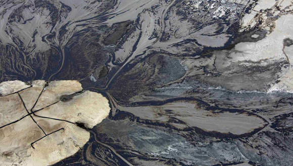 Petróleo entra en un estanque de relaves (desechos tóxicos subproductos de procesos mineros) en las arenas alquitranadas de la empresa de energía Suncor, cerca de Fort McMurray, Alberta (Canadá). Foto: Reuters