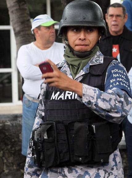 Un policía de la Marina toma fotos a los cubanos. Foto: Ismael Francisco/Cubadebate.