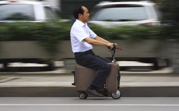 He Liang maneja su moto-maleta casera en una calle en la provincia china de Hunan este 28 de mayo de 2014. Liang ha pasado 10 años modificando esta valija para convertirla en un vehículo motor que puede alcanzar lo