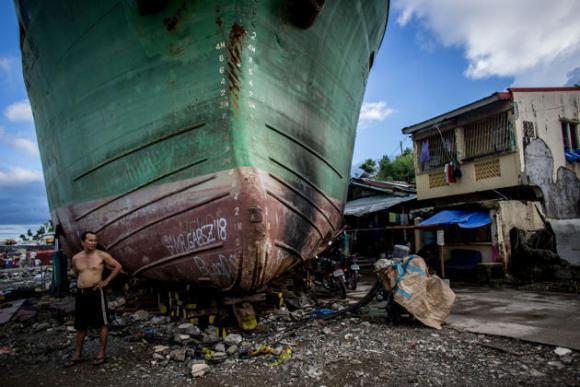 Un hombre posa frente a un barco que fue arrastrado a tierra por el tifón Haiyan el 18 de abril de 2014 en Tacloban, Leyte, Filipinas. (Photo by Chris McGrathGetty Images)