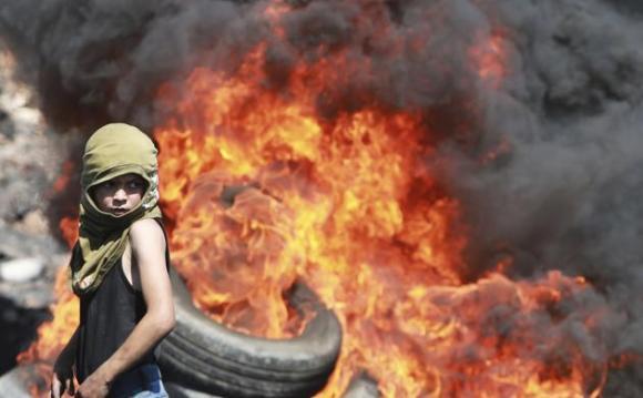 Un niño palestino mira de cerca la quema de neumáticos durante los enfrentamientos con soldados israelíes a raíz de una protesta cerca del asentamiento judío de Qadomem este 19 de septiembre 2014 .REUTERSAbed Omar