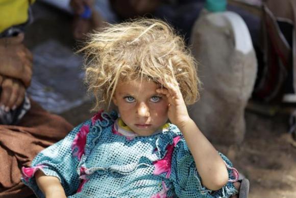 Una niña de la etnia minoritaria yazidi, oriunda de la población iraquí de Sinjar y que huye de la persecución de combatientes del Estado Islámico, es fotografiada en el cruce fronterizo entre Irak y Siria, en Fish