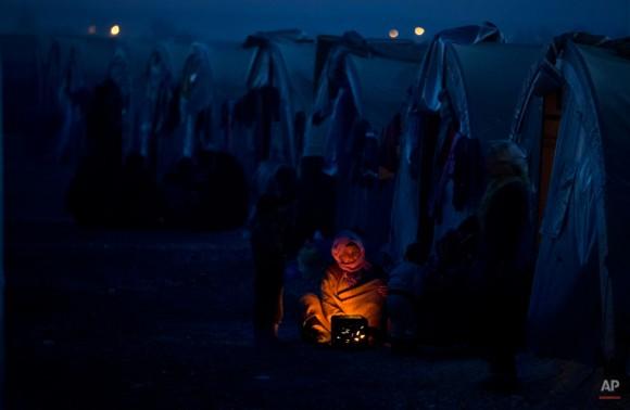 Una mujer kurda de Siria ancianos refugiados de la zona Kobani, se calienta por un incendio en un campamento en Suruc, en la frontera entre Turquía y Siria Lunes, 10 de noviembre de 2014. Kobani, también conocido como Ayn árabe, y sus alrededores, tiene estado bajo asalto por los extremistas del grupo Estado Islámico desde mediados de septiembre y está siendo defendida por combatientes kurdos. (AP Photo / Vadim Ghirda)