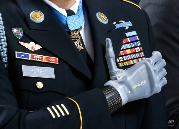 """Medalla de Honor sargento destinatario. Primera clase Leroy Petry se encuentra con su prótesis de mano sobre su corazón, con su Medalla de Honor durante el """"Juramento de Lealtad"""" en el Capitolio en Olympia, Washington. El miércoles 2 de abril de 2014 durante una ceremonia a él ya otros destinatarios honrar de la Medalla de Honor del estado de Washington. Petry perdió su mano en 2008, cuando una granada enemiga que estaba lanzando lejos de compañeros soldados detonaron en combate en Afganistán. (Foto AP / Ted S. Warren)"""