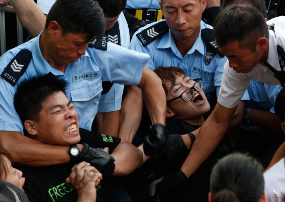 Los manifestantes están llevados por los agentes de policía después de que cientos de manifestantes protagonizaron una sentada pacífica ins durante la noche en una carretera en el distrito financiero de Hong Kong Miércoles, 02 de julio 2014, a raíz de una gran manifestación para mostrar su apoyo a las reformas democráticas y oponerse a la voluntad de Beijing tener la última palabra sobre los candidatos a empleo del jefe del ejecutivo. (Foto AP / Kin Cheung)