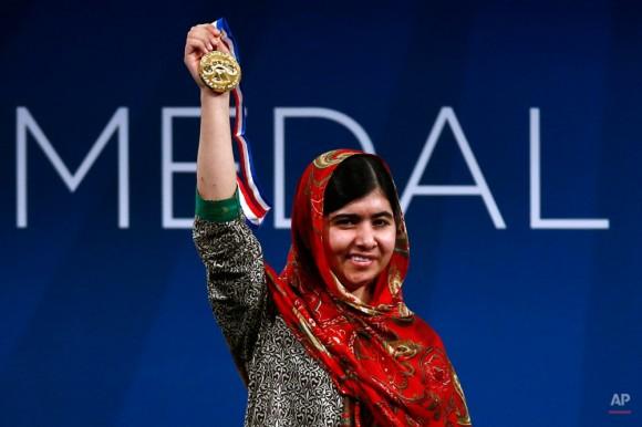 Malala Yousafzai sostiene su Medalla de la Libertad durante una ceremonia en el Centro Nacional de la Constitución, Martes, 21 de octubre 2014, en Filadelfia. El honor se otorga anualmente a un individuo que muestra coraje y convicción mientras se esfuerza por asegurar la libertad de las personas en todo el mundo. (AP Photo / Matt Rourke)