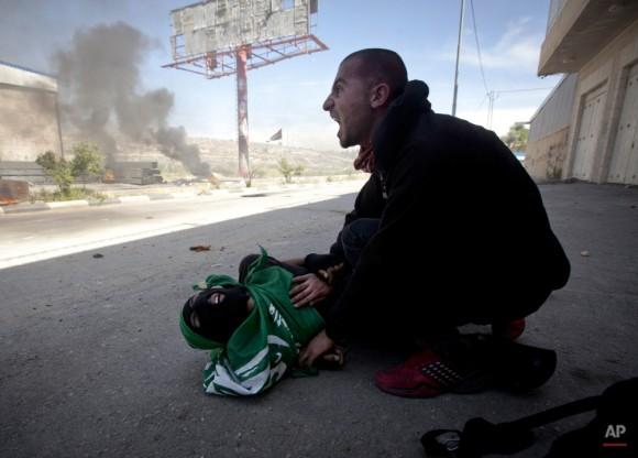 Un palestino grita por ayuda momentos después adolescente palestino, Mohammad Abu Daher, en la planta, fue muerto a tiros por soldados israelíes cerca de la ciudad cisjordana de Ramallah, jueves, 15 de mayo de 2014. Las autoridades médicas dicen que las tropas israelíes mataron a dos palestinos adolescentes en un choque de Cisjordania que se desató después de palestinos conmemoraron el aniversario de su desarraigo en la guerra por el 1948 la creación de Israel. (Foto AP / Majdi Mohammed)